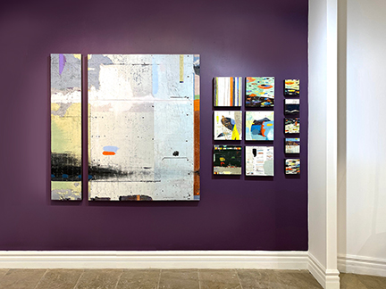 Paintings hung on a purple wall